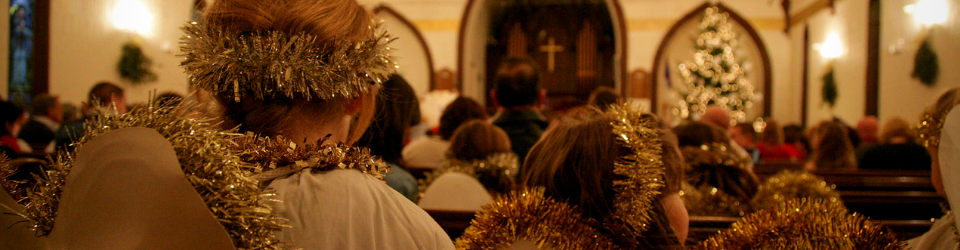 two children dressed as angels seated and watching the Christmas Eve service at First Church